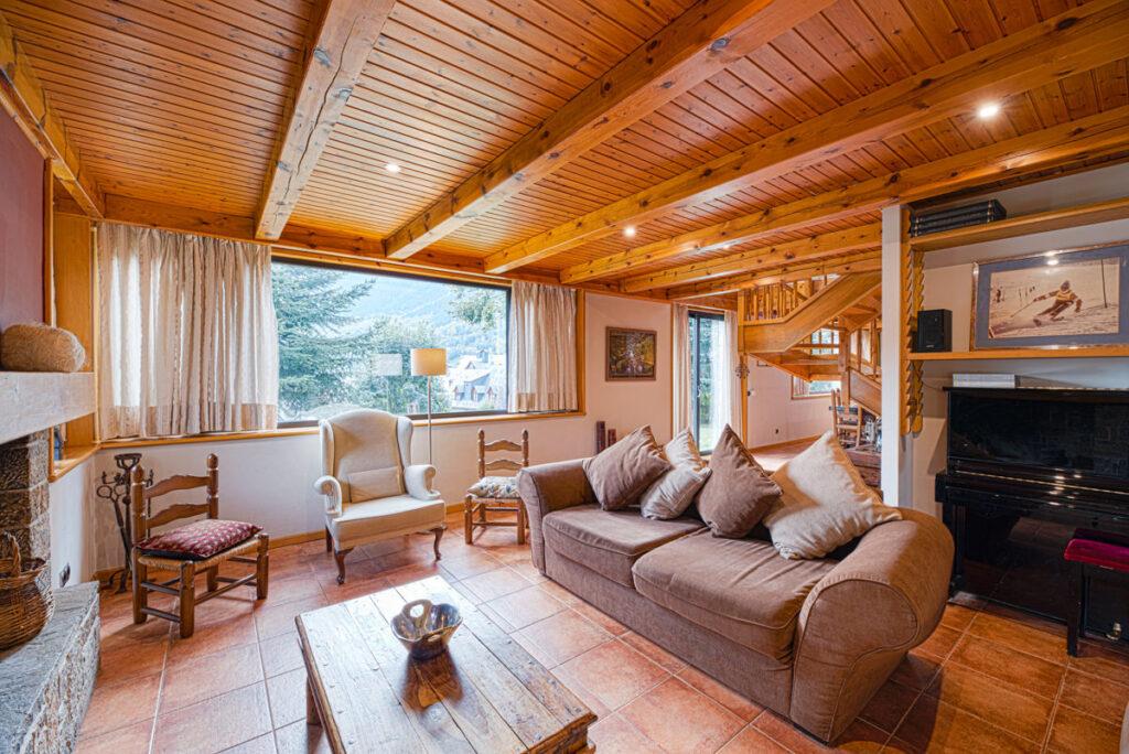 salón con chimenea, piano y vistas al jardín de la casa